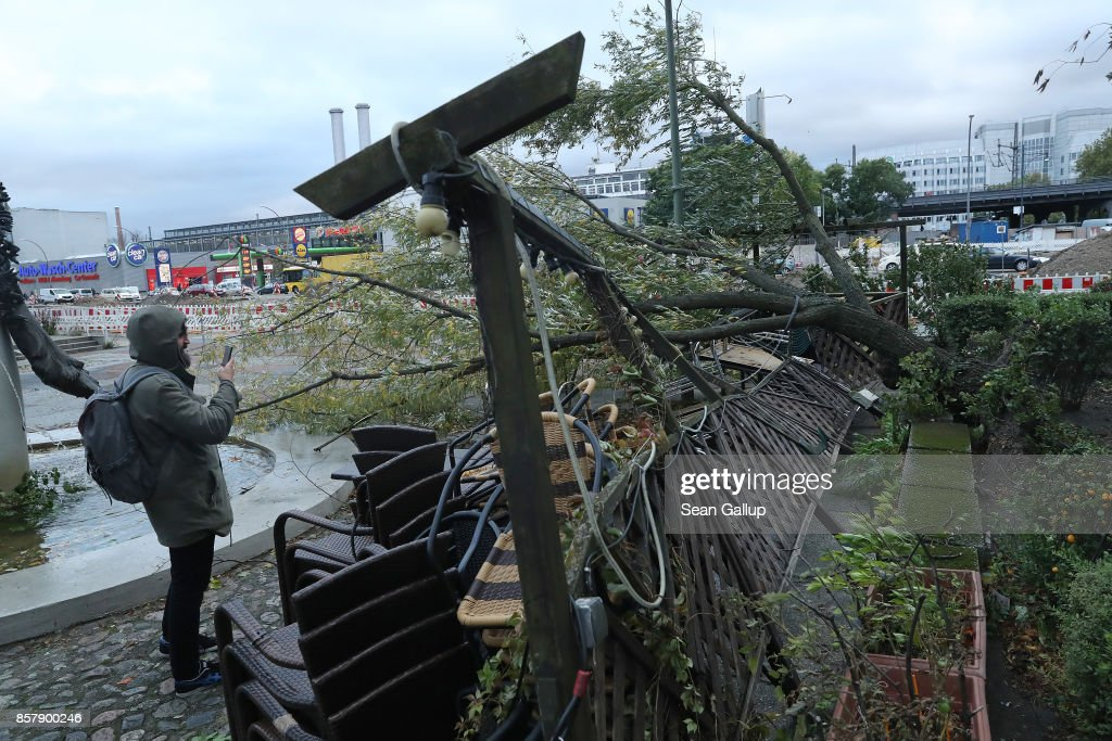 A man stops to photograph a tree that was uprooted and smashed a restaurant's outdoor patio during a storm front on October 5, 2017 in Berlin, Germany. Storm front 'Xavier' is hitting northern and central Germany hard, leading to the closure of airports, rail lines, commuter trains and buses and even highways across the region. Authorities are reporting two deaths so far, both in Brandenburg state.