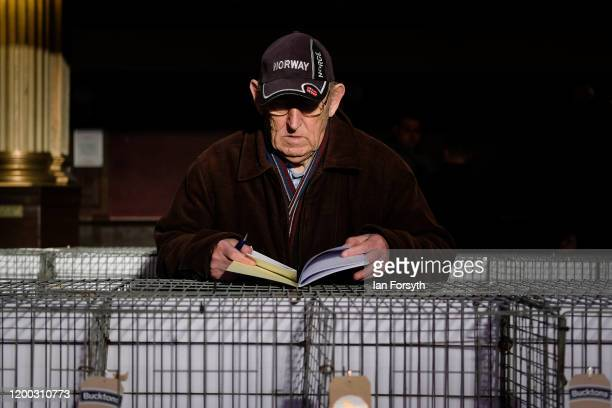 A man stops to take notes on some of the pigeons on the first day of the annual British Homing Pigeon World Show of the Year at Blackpool Winter...
