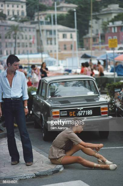 A man stops to watch a young woman tie her sandals on the pavement in Portofino marina August 1977