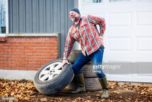 大型トラック タイヤを持ち上げる彼の背中に負担をかける男