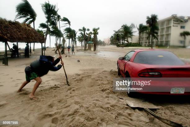 A man stranded in the wake of Hurricane Wilma attempt to dig out their car as the eye passes on October 24 2005 over Deerfield Beach Forida Hurricane...