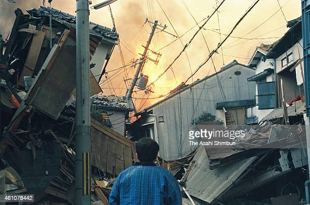 A man strands on the street watching the fire breaks out after the strong earthquake on January 17 1995 in Kobe Hyogo Japan Magnitude 73 strong...