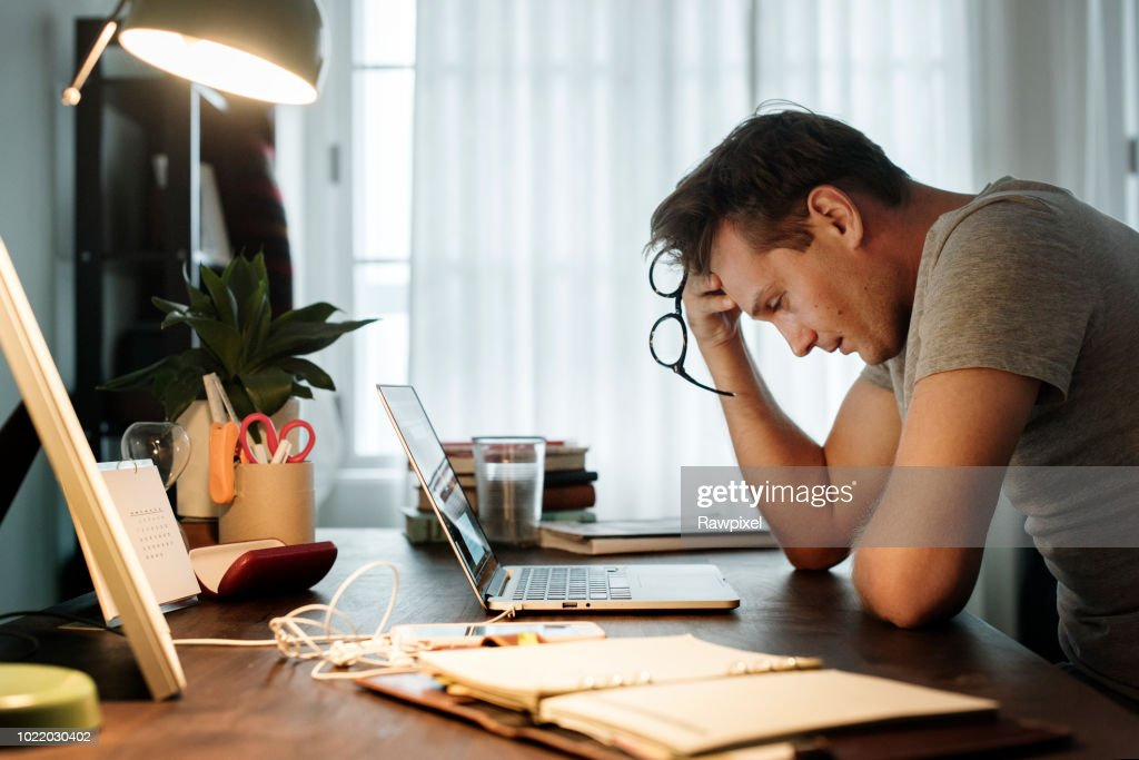 Man stressed while working on laptop : Stock Photo