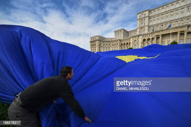 A man stretches a giant flag of the European Union in front of the Parliament building in Bucharest May 9 2013 A private TV station installed a EU...