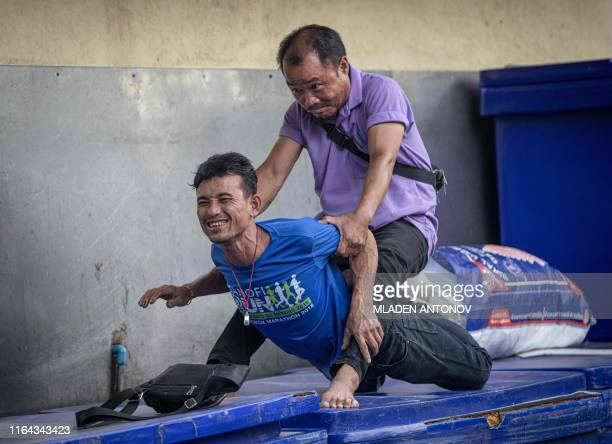 A man stretches another man during a massage session on a street in Bangkok on August 27 2019