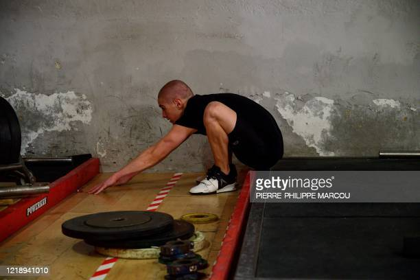 Man stretches at the Sideropolis weightlifting gym in Madrid on June 9, 2020 after gyms reopened as the country continues to loosen a national...