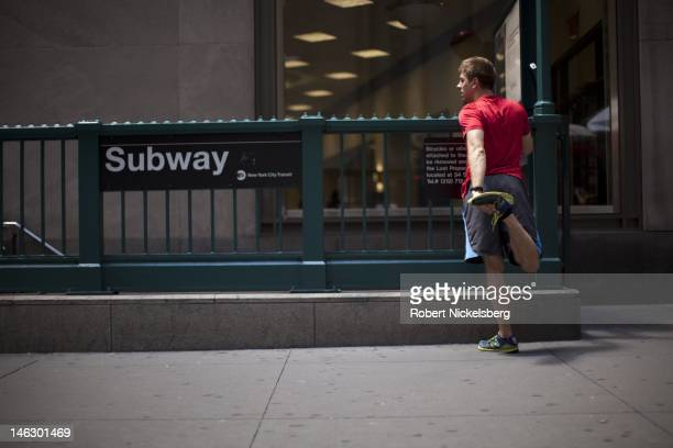 A man stretches before a workout June 7 2012 on Wall Street near the New York Stock Exchange in New York City