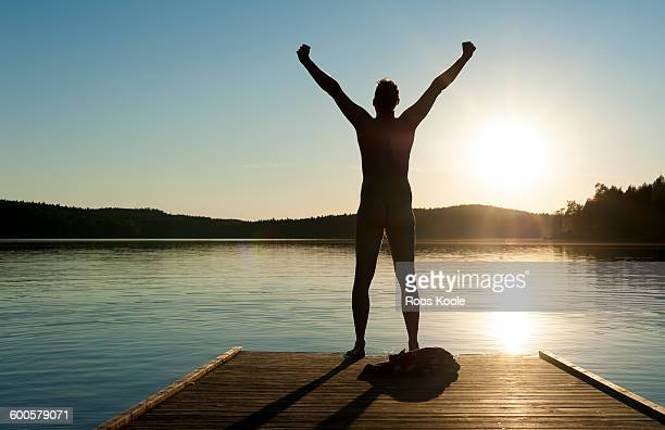 A man stretches his arms on a jetty