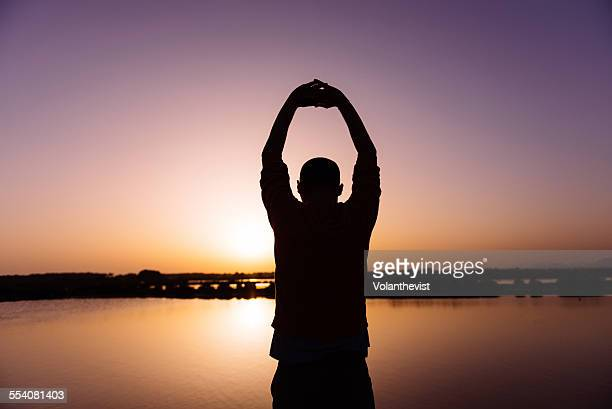 Man stretching arms in Majorca at sunset