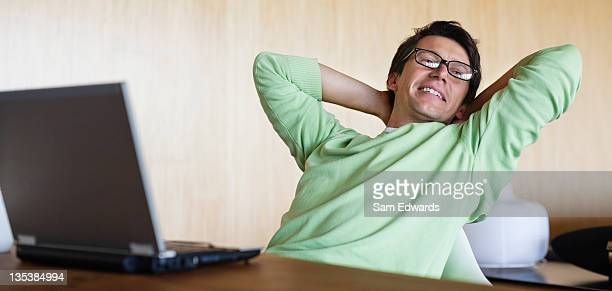 Mann stretching am Schreibtisch mit laptop