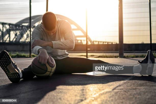 Man stretching before basketball game with morning sun in background
