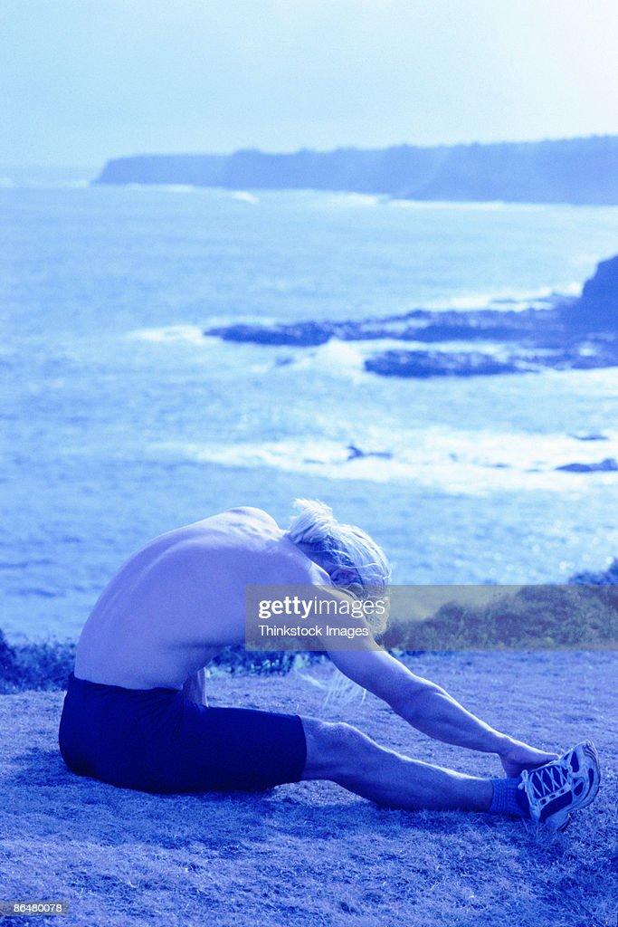 Man stretching by coast : Stock Photo