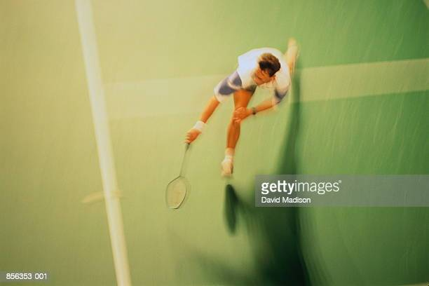 Man stretching for shot during game of badminton, overhead view