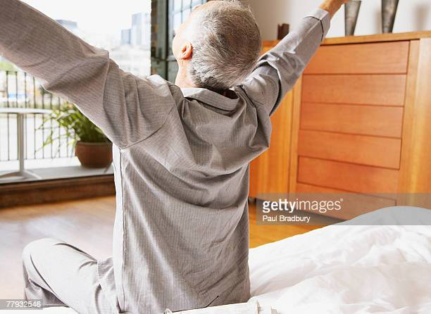 Man stretching getting out of bed