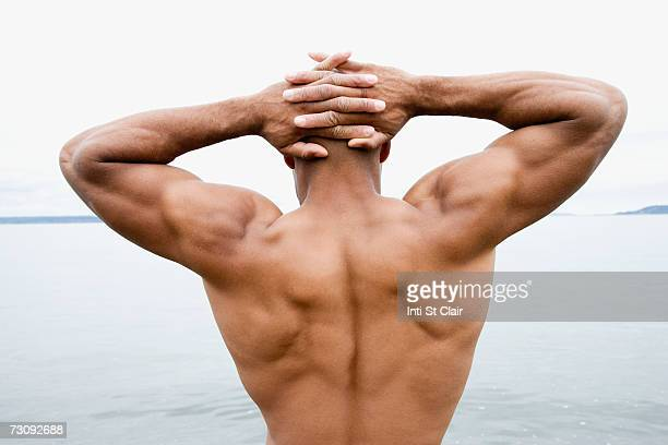 Man stretching hands behind head, rear view