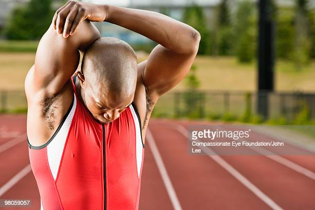 Man stretching his muscles beside a running track