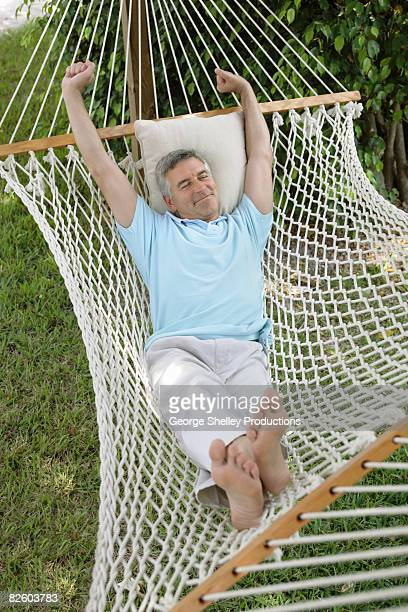 man stretching in a hammock - only mature men stock pictures, royalty-free photos & images