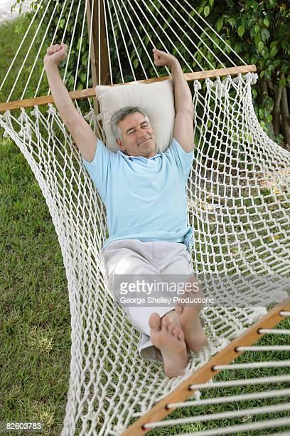 Man stretching in a hammock