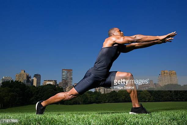 man stretching in central park - center athlete stock pictures, royalty-free photos & images