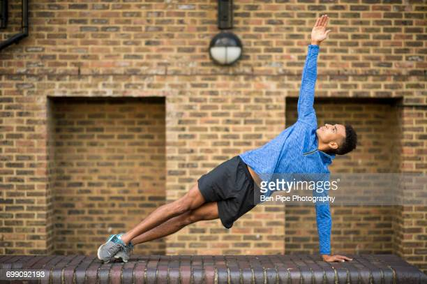 man stretching in front of brick wall, wapping, london, uk - running shorts stock pictures, royalty-free photos & images