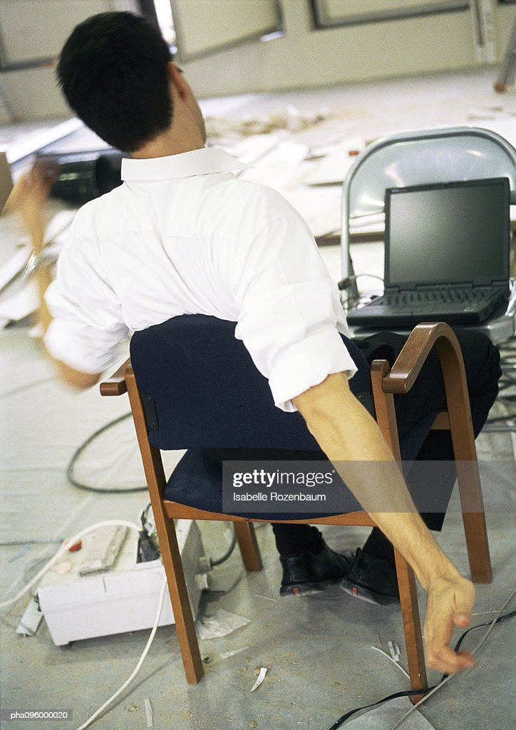 Man stretching in front of laptop computer : Stockfoto