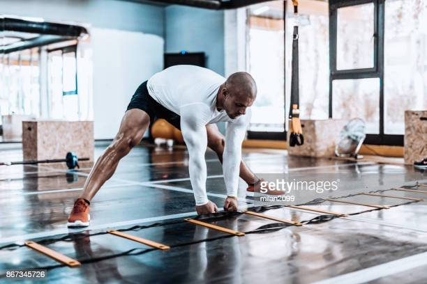 man stretching in the gym before exercise - milan2099 stock photos and pictures
