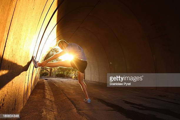 Man stretching in tunnel at sunset