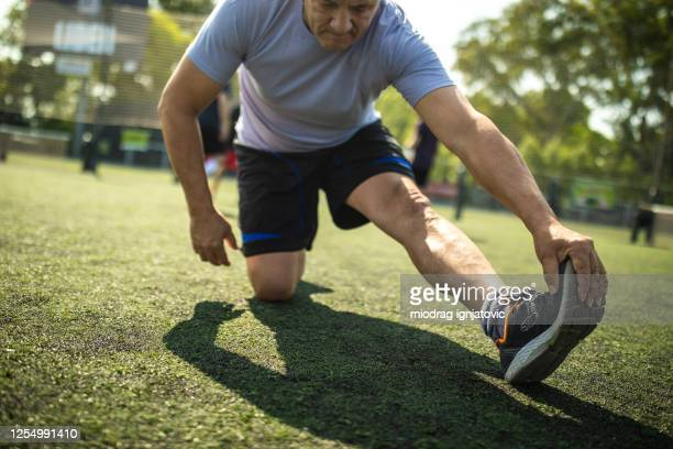 man stretching legs at soccer court during sunny day in buenos aires - warming up stock pictures, royalty-free photos & images