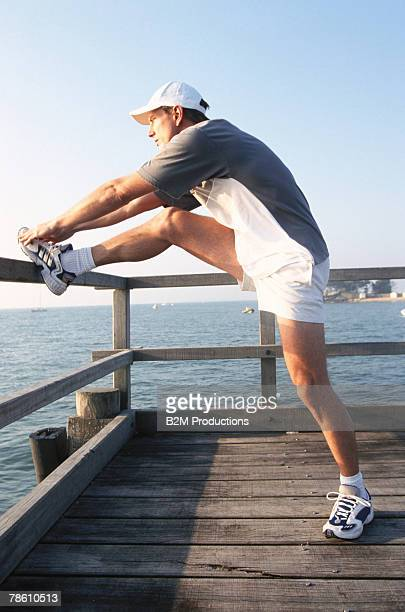 Man stretching on boardwalk