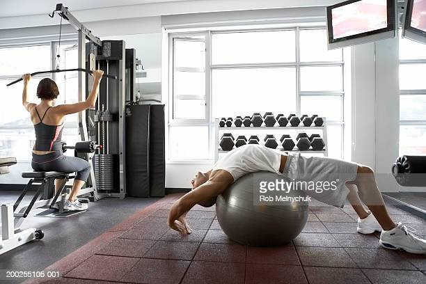 Man stretching on fitness ball, woman lifting weights in background