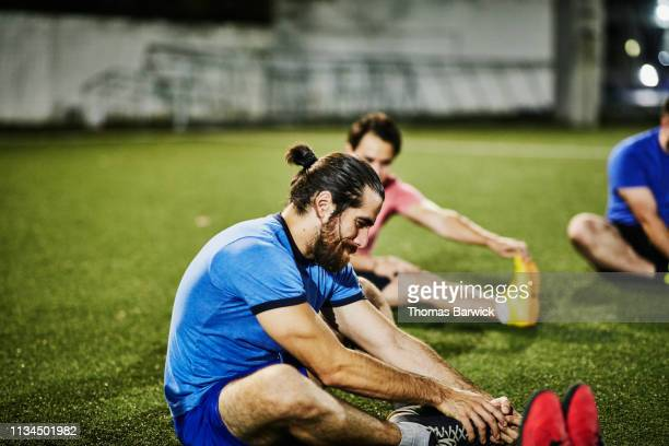 man stretching on soccer field with friends before evening soccer match - team sport stock pictures, royalty-free photos & images