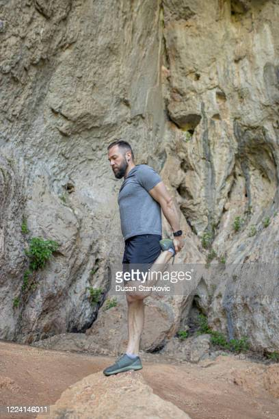 man stretching on the mountains - dusan stankovic stock pictures, royalty-free photos & images