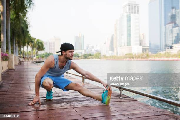 Man stretching on walkway by river against buildings