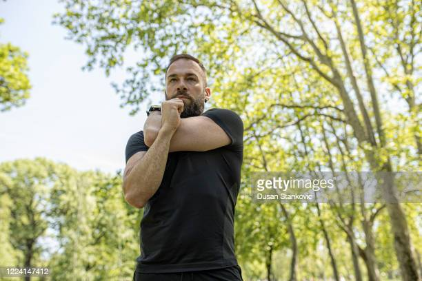 man stretching outdoors. active and healthy lifestyle - dusan stankovic stock pictures, royalty-free photos & images