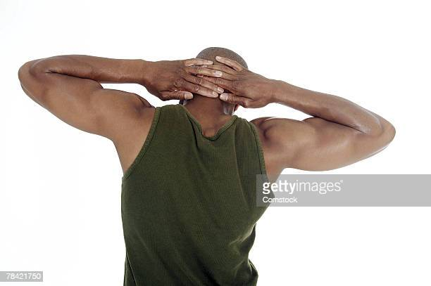 Man stretching with hands behind head