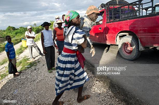 A man stricken by cholera is helped by his mother to a pickup truck at PontSonde 120km north of PortauPrince on October 27 2010 to bring to hospital...