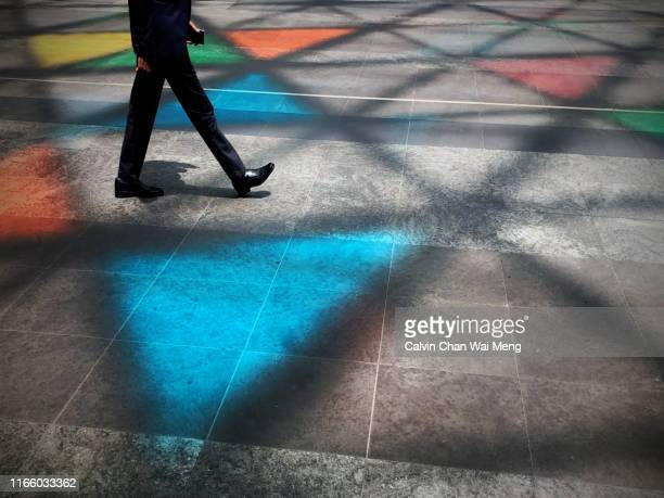 man striding across colorful street - multi colored suit stock pictures, royalty-free photos & images