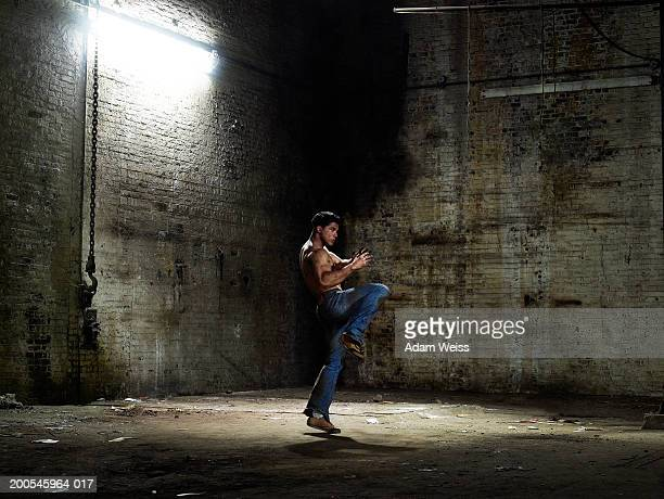 Man striking fighting stance in empty industrial space