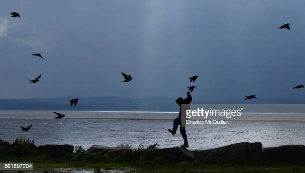 A man struggles against the wind as a flock of birds fly past on Mount Charles pier ahead of Hurricane Ophelia on October 16 2017 in Donegal Ireland...