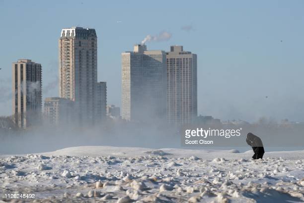 A man struggles in the wind and cold as he walks along North Avenue Beach on January 30 2019 in Chicago Illinois Businesses and schools have closed...