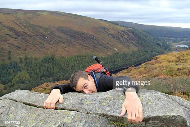 Man struggles while rock climbing