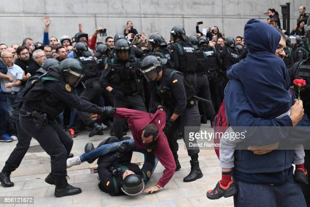 A man struggles with the police as other police take hold of a man and a child holding a red flower as they move in on the crowds as members of the...