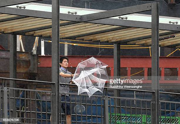 A man struggles with umbrella in the wind and rain delivered by Typhoon Halong on August 10 2014 in Himeji Japan The Japan Meteorological Agency has...