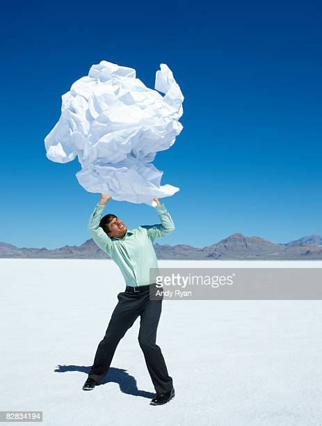 Man Struggling to Hold Up Giant Wad of Paper