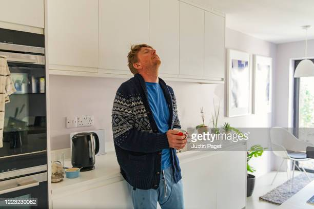 man struggling with flu like symptoms in the kitchen - cold and flu stock pictures, royalty-free photos & images