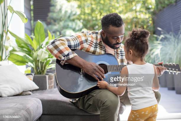 man strumming a guitar in front of his young daughter - simple living stock pictures, royalty-free photos & images
