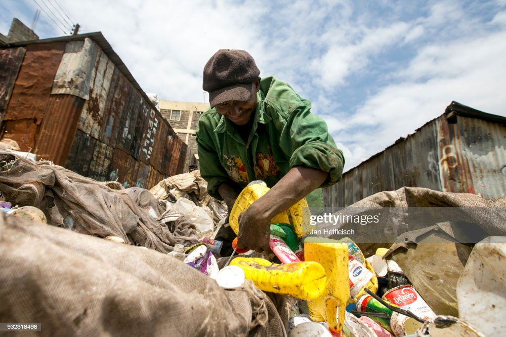A man stuck plastic bottles into a bag at the Dandora rubbish dump. on March 14, 2018 in Nairobi, Kenya. The Dandora landfield is located 8 Kilometer east of the city center of Nairobi, the capital of Kenya. Every day, more than 2.000 metric tonnes of waste are dumped on this site. More than 3000 pickers work day by day at the sprawling 30-acre rubbish dump.