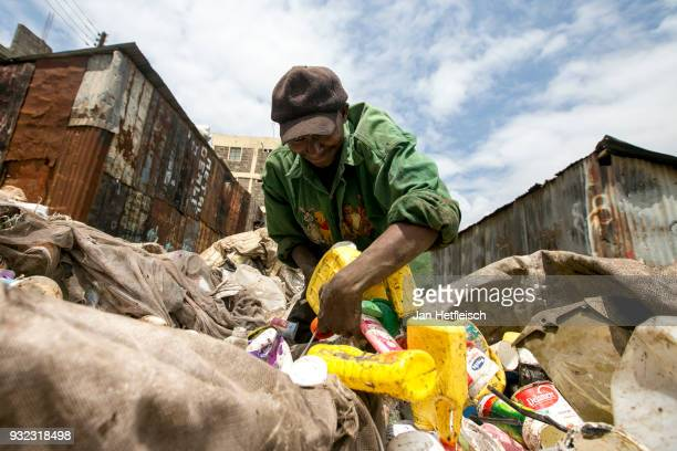 A man stuck plastic bottles into a bag at the Dandora rubbish dump on March 14 2018 in Nairobi Kenya The Dandora landfield is located 8 Kilometer...