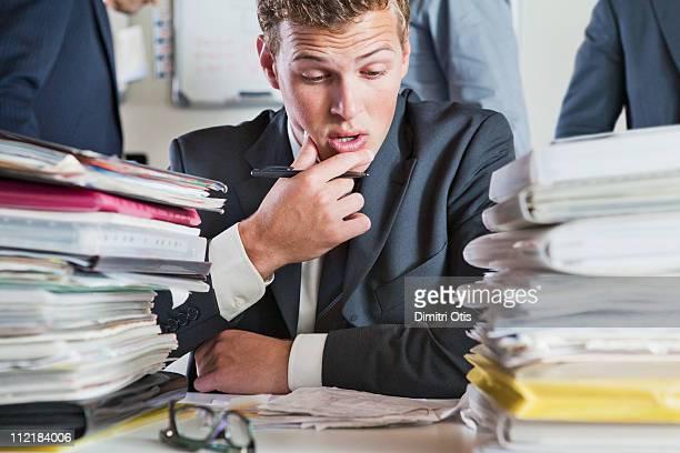 man studying paperwork with worried expression - rechnungswesen stock-fotos und bilder