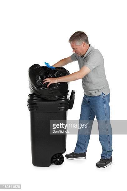 Man Stuffing Trash into Garbage Bin